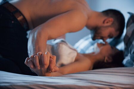 Passion and love. Sexy couple lying on the bed and enjoying themselves at morning time. Reklamní fotografie