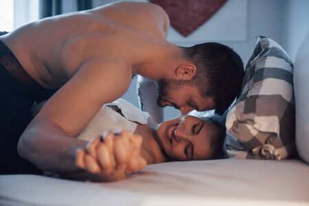 True passion. Sexy couple lying on the bed and enjoying themselves at morning time.
