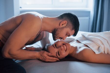 Man sitting and kissing his woman. Sexy couple lying on the bed and enjoying themselves at morning time.