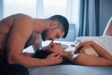 Young and happy. Sexy couple lying on the bed and enjoying themselves at morning time.
