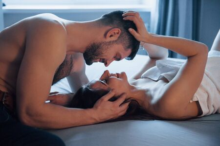 Smiling together. Sexy couple lying on the bed and enjoying themselves at morning time. Reklamní fotografie