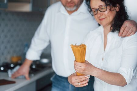 Holding spaghetti. Man and his wife in white shirt preparing food on the kitchen using vegetables.