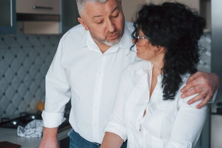 Talking about something. Man and his wife in white shirt preparing food on the kitchen using vegetables.