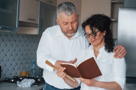 Using book with recipes. Man and his wife in white shirt preparing food on the kitchen using vegetables. Zdjęcie Seryjne