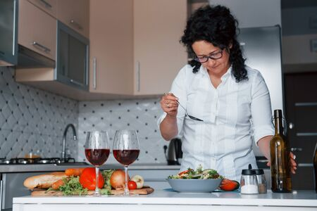 Just few moves and it will be ready for eat. Woman in white shirt preparing food on the kitchen using vegetables.