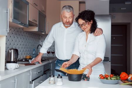 Enough for us. Man and his wife in white shirt preparing food on the kitchen using vegetables. Imagens