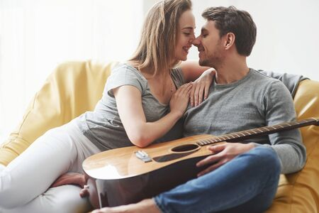 Giving a kiss. Guitar on the legs. Happy couple relaxing on the yellow sofa in the living room of their new house. Zdjęcie Seryjne
