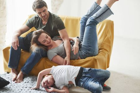 Kid lying on the floor. Happy family have fun on the yellow sofa in the living room of their new house.