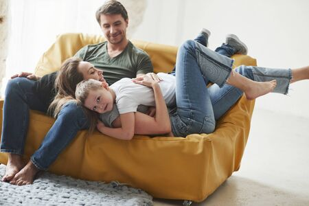 Cute hugs. Happy family have fun on the yellow sofa in the living room of their new house. Zdjęcie Seryjne