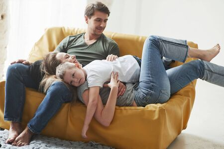 Conception of succesful people. Happy family have fun on the yellow sofa in the living room of their new house. Zdjęcie Seryjne