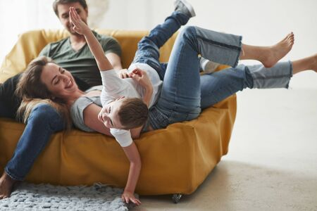 Kid imagine that he is airplane. Happy family have fun on the yellow sofa in the living room of their new house.
