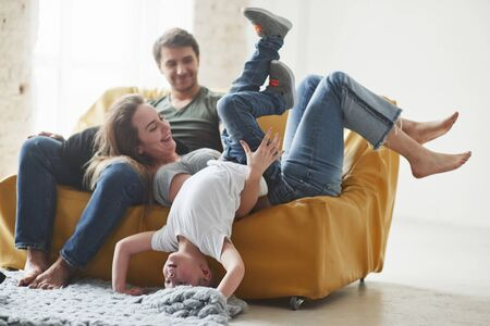 Having leisure. Happy family have fun on the yellow sofa in the living room of their new house.