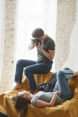 Photographer taking a shot of young girl that lying on the white sofa. Zdjęcie Seryjne