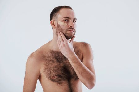 Heres what happening when you shave your beard not carefully. Man with bare chest stands against white background in the studio.
