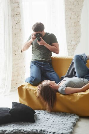 Backstage conception. Photographer taking a shot of young girl that lying on the white sofa. Zdjęcie Seryjne