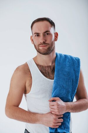 Going to the shower. Man with blue towel stands against white background in the studio. Фото со стока