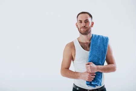 Healthcare conception. Man with blue towel stands against white background in the studio.