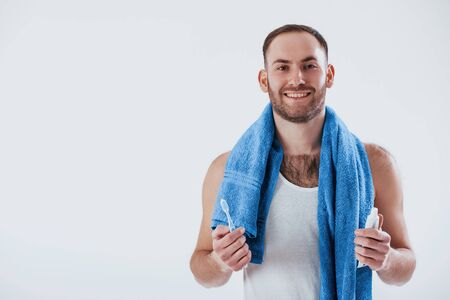 Toothbruh in hand. Man with blue towel stands against white background in the studio. Standard-Bild