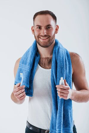 Teeth care. Man with blue towel stands against white background in the studio. Фото со стока