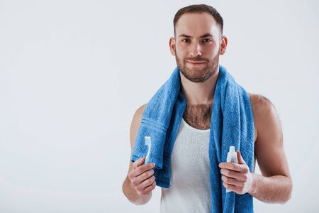 Clean your teeth every day. Man with blue towel stands against white background in the studio. Фото со стока