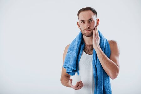 Ready for the shaving. Man with blue towel stands against white background in the studio. Фото со стока