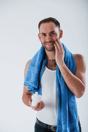 Sincere smile when using cream for shaving. Man with blue towel stands against white background in the studio.