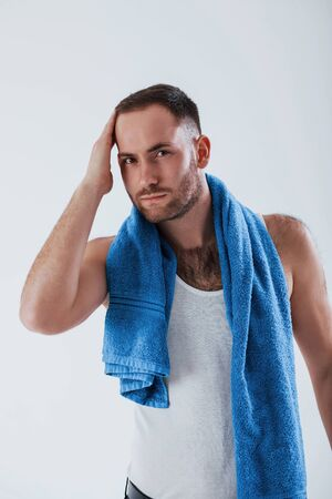 Male model taking care of himself. Man with blue towel stands against white background in the studio. Imagens