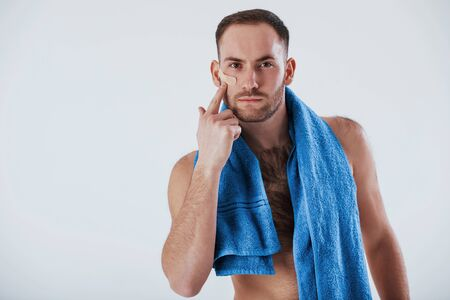 Scratch on face. Man with blue towel stands against white background in the studio. Фото со стока