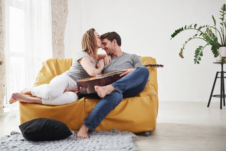 Thankful girlfriend gives a kiss. Happy couple relaxing on the yellow sofa in the living room of their new house.