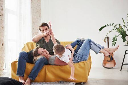 Kid lying on his parents. Happy family have fun on the yellow sofa in the living room of their new house.
