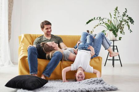 Child fools around. Happy family have fun on the yellow sofa in the living room of their new house. Zdjęcie Seryjne