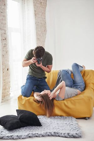 In casual clothes. Photographer taking a shot of young girl that lying on the white sofa.