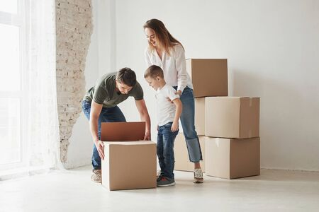Lets take this out. Family have removal into new house. Unpacking moving boxes. Stock Photo
