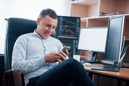 Reading some good news. Man working online in the office with multiple computer screens in index charts. Stock fotó