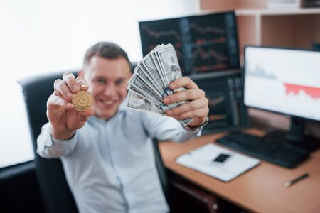 Success concept. Businessman holding bitcoin and money in hands while sitting in modern office with many monitors with graphs.