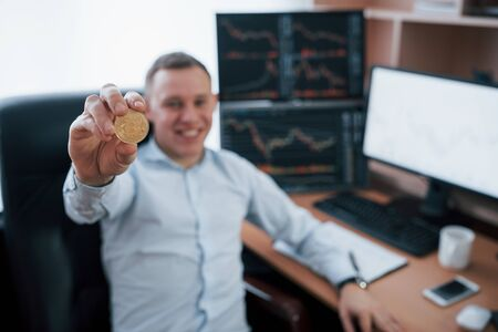 Shows physical sample. Businessman holding bitcoin in hand while sitting in modern office with many monitors with graphs.