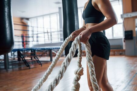 Everyday challenge. Blonde sport woman have exercise with ropes in the gym. Strong female.