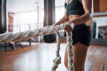 Power and health. Blonde sport woman have exercise with ropes in the gym. Strong female.