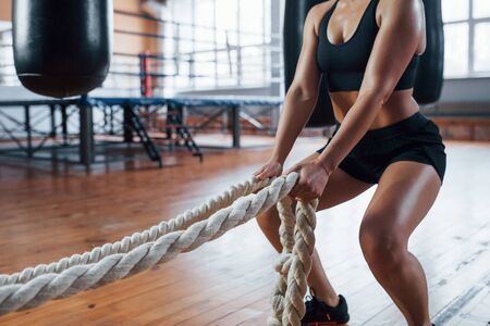 Productive exercise. Blonde sport woman with ropes in the gym. Strong female. Stock fotó