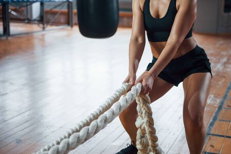 Holds white ropes. Blonde sport woman have exercise in the gym. Strong female. Stock fotó