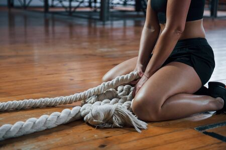 Wooden floor. Blonde sport woman have exercise with ropes in the gym. Strong female. Stock fotó