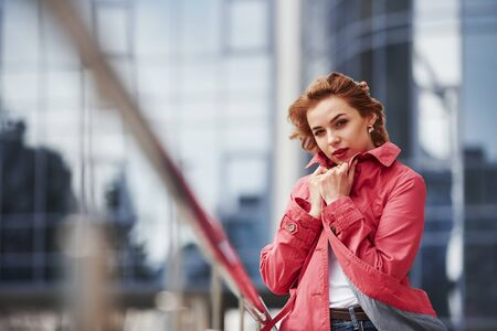 Its cold out there. Adult pretty woman in warm red coat have walk in the city at her weekends time.