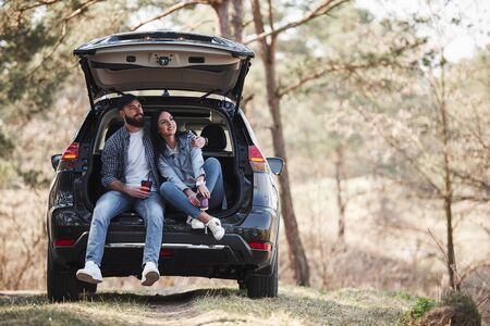 Having a break. Sitting on rear part of automobile. Enjoying the nature. Couple have arrived to the forest on their brand new black car. Imagens