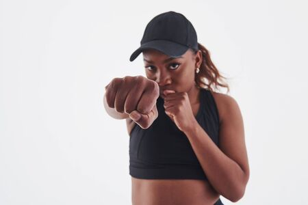 Throwing a punch. Young beautiful afro american woman in the studio against white background.