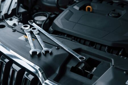 Black colored interior. Repair tools lying down on the engine of automobile under the hood.