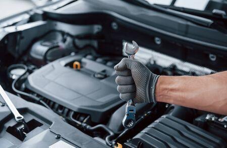Alles wird behoben. Die Hand des Mannes im Handschuh hält einen Schraubenschlüssel vor einem kaputten Auto.