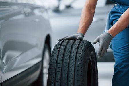 Le client n'attendra pas. Mécanicien tenant un pneu au garage de réparation. Remplacement des pneus hiver et été. Banque d'images