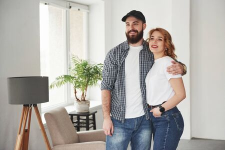 Happy couple together in their new house. Conception of moving.