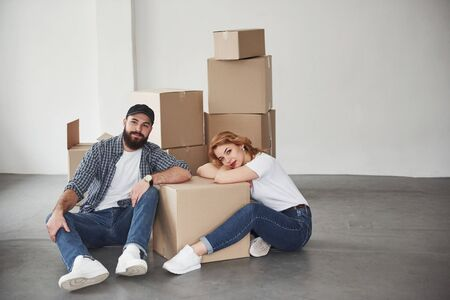 Looking straight into the camera. Happy couple together in their new house. Conception of moving. Stock Photo