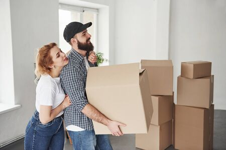 Tells what to do. Happy couple together in their new house. Conception of moving.